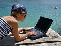 Mädchen mit Sonnenbrillen und Laptop auf Meer Stockfotos