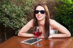 Mädchen mit Sonnenbrillen Wein auf Terrasse genießend Stockbild