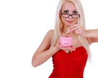 Mädchen mit Sparschwein, intelligentes blondes Einsparungsgeld der jungen Frau lokalisiert Lizenzfreie Stockfotos