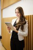 Mädchen mit Tablet-Computer in den Händen nähern sich Wand stockfoto