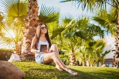 Mädchen mit Tablette im Palmengarten Lizenzfreies Stockbild