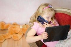 Mädchen mit Tablette und Handy Stockfoto