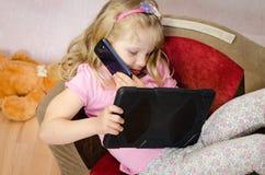 Mädchen mit Tablette und Handy Stockbilder