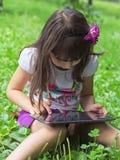 Mädchen mit Tabletten-PC in der Wiese Lizenzfreie Stockfotos