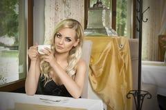 Mädchen mit Tasse Tee im Weinlesecafé Lizenzfreies Stockfoto
