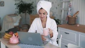M?dchen mit Tuch auf dem Kopf, der Videoschw?tzchen auf Laptop und Getr?nken Tee, Zeitlupe hat stock footage