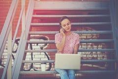 Mädchen mit Unterhaltungstelefon des Laptops Lizenzfreie Stockbilder