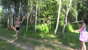 Mädchen mit Vaterspieltennis mit dem Federballschläger im Freien stock video footage
