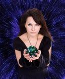 Mädchen mit Vermögenserklärenkugel gegen Sternhimmel. Lizenzfreies Stockbild