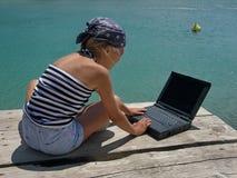 Mädchen mit Verpackung und Laptop auf Meer Lizenzfreie Stockbilder