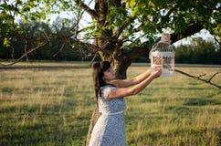 Mädchen mit Vogelkäfig Stockbilder