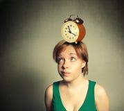 Mädchen mit Wecker auf Kopf Stockbilder