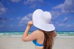 Mädchen mit weißem Sonnehuthimmel und carribean Meer stockfotografie