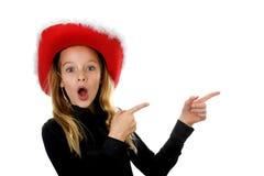 Mädchen mit Weihnachtshut schaut überrascht Stockfotos