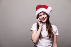 Mädchen mit Weihnachtshut um Telefon ersuchend Lizenzfreie Stockbilder