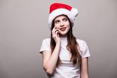 Mädchen mit Weihnachtshut um Telefon ersuchend Stockfotos