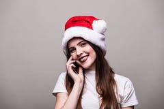 Mädchen mit Weihnachtshut um Telefon ersuchend lizenzfreie stockfotografie
