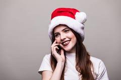 Mädchen mit Weihnachtshut um Telefon ersuchend Stockbilder