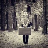 Mädchen mit Weinlesekoffer und Kamera, die im Wald und im Klo steht Stockbilder