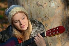 Mädchen mit woolen Kappe und Gitarre Lizenzfreie Stockbilder