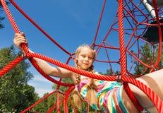 Mädchen mit zwei Borten sitzt auf Seilen des roten Netzes Lizenzfreie Stockfotos