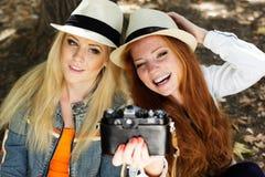 Mädchen mit zwei Jugendlichen, das selfe mit Kamera nimmt Stockbilder