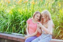 Mädchen mit zwei Jugendlichen mit Telefon Stockfotos