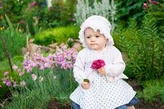 Mädchen 8 Monate alte europäische ukrainische kleine Baby auf einem Weg im Garten hält eine Blume und Erdbeeren in ihren Händen Lizenzfreie Stockfotografie