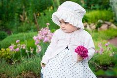 Mädchen 8 Monate alte europäische ukrainische kleine Baby auf einem Weg im Garten hält eine Blume und Erdbeeren in ihren Händen Stockfotos