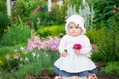 Mädchen 8 Monate alte europäische ukrainische kleine Baby auf einem Weg im Garten hält eine Blume und Erdbeeren in ihren Händen Lizenzfreies Stockfoto