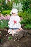 Mädchen 8 Monate alte europäische ukrainische kleine Baby auf einem Weg im Garten hält eine Blume und Erdbeeren in ihren Händen Stockfotografie