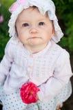 Mädchen 8 Monate alte europäische ukrainische kleine Baby auf einem Weg im Garten hält eine Blume und Erdbeeren in ihren Händen Stockfoto