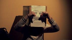 Mädchen nachts einen Kasten mit einer unglücklichen Gesichtszeichnung auf ihrem Kopf tragend Konzept der Sorge und der Traurigkei stock video
