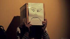 Mädchen nachts einen Kasten mit einer unglücklichen Gesichtszeichnung auf ihrem Kopf tragend Konzept der Sorge und der Traurigkei stock video footage