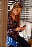 Mädchen nahe dem Fenster, das im Handy schaut Lizenzfreie Stockfotos
