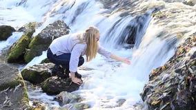 Mädchen nahe dem Wasserfall berührt das Wasser stock video footage