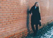 Mädchen nahe der Backsteinmauer stockbild