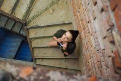 Mädchen nahe der Backsteinmauer in der Militärart stockfotos