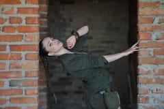 Mädchen nahe der Backsteinmauer in der Militärart lizenzfreie stockfotografie