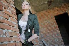 Mädchen nahe der Backsteinmauer in der Militärart lizenzfreie stockfotos