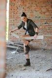 Mädchen nahe der Backsteinmauer in der Militärart stockfotografie