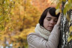 Mädchen nahe einem Baum gegen einen Hintergrund des Herbstlaubs Lizenzfreie Stockfotografie
