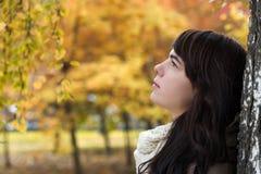 Mädchen nahe einem Baum gegen einen Hintergrund des Herbstlaubs Lizenzfreie Stockfotos