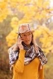 Mädchen nahe Herbstbaum mit Telefon Stockbild