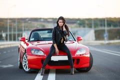 Mädchen nahe rotem Auto Stockbilder