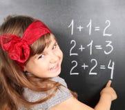 Mädchen nahe Tafel Mathematik erlernend Stockfotografie