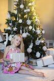 Mädchen nahe Weihnachtsbaum mit Geschenken und Spielwaren, Kästen, Weihnachten, neues Jahr, Lebensstil, Feiertag, Ferien, Wartesa Lizenzfreie Stockfotografie