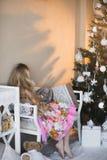 Mädchen nahe Weihnachtsbaum mit Geschenken und Spielwaren, Kästen, Weihnachten, neues Jahr, Lebensstil, Feiertag, Ferien, Wartesa Stockfoto