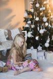 Mädchen nahe Weihnachtsbaum mit Geschenken und Spielwaren, Kästen, Weihnachten, neues Jahr, Lebensstil, Feiertag, Ferien, Wartesa Stockbilder