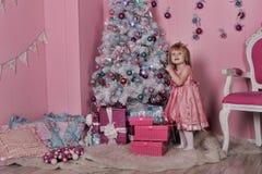 Mädchen nahe Weihnachtstannenbaum Stockbilder